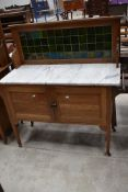 An Arts and Crafts style golden oak washstand, having marble top and tiled back, width approx. 122cm