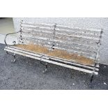 A traditional garden bench having metal frame and scroll arms, wood slat seat and back beginning