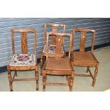 A set of four early to mid golden oak dining chairs, two having tapestry seats