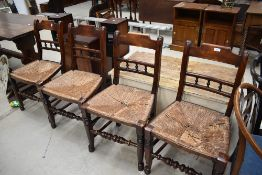 A set of four 19th Century spindle back kitchen chairs having rush seats