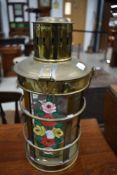A traditional brass storm or barge lantern having romany style painted decoration to glass