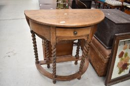 A traditional oak demi lune hall table, having twist gate leg and back flap, width approx. 77cm
