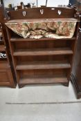 An Arts and Crafts dark oak bookcase with heart motif decoration