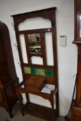 A late 19th Century oak hall stand having mirror and part tiled back, compartment and double drip