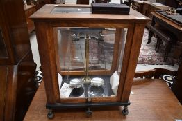 A traditional oak cased set of lab scale and cased set of weights