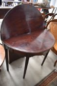 A 19th Century mahogany and inlaid fold over tea table, of demi lune form, on tapered legs, nice