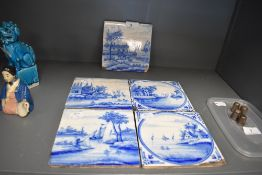 Five antique Dutch delft tiles depicting river side or canal scenes most having age related wear