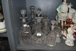 A selection of early to late Victorian spirit bottles and decanters including cut and moulded glass