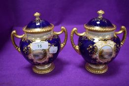 A pair of Coalport twin handle urns or trophy having cobalt blue glaze and gilt detailing with