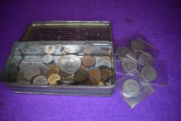 A selection of collectable world coins and currency in vintage tin