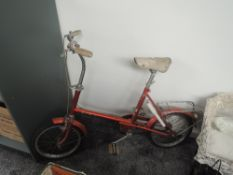 A 1970's Raleigh RSW14 Childs Bicycle in red with white leather seat, pump and bell present
