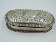 A Victorian silver trinket box of oval form having crimped rims and moulded decoration to hinged