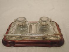 A modern silver pen and ink stand having a pair of glass bottles with decorative silver lids with
