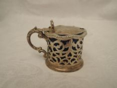 A Victorian silver lidded mustard pot having pierced decoration, moulded bow thumb rest and blue