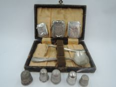 A small selection of HM silver including three vestas, a cased baby's first cutlery set, and five HM
