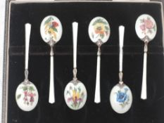 A cased set of six silver and enamel teaspoons having floral pictorial decoration to back of gilt