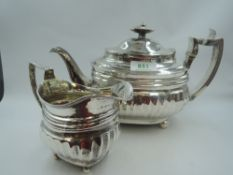 A Georgian silver teapot and sugar bowl of waisted oval form having fluted decoration, bun feet