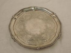 A Victorian silver salver having gadrooned pie crust rim, engraved decoration with central crest and