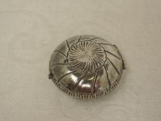 A white metal circular trinket box of oyster shell style having gilt interior and bearing marks to