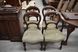 A set of four Victorian mahogany balloon back chairs having turned legs and later green dralon