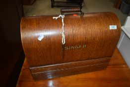 A vintage Singer sewing machine, in oak dome top case