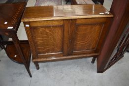 An early 20th Century oak cabinet of slender form having lift flap top and double cupboard doors,