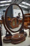A Victorian mahogany toilet mirror having scroll frame and trinket base
