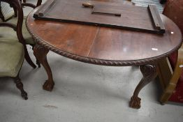 A late 19th or early 20th Century mahogany wind out dining table having oval top with gadrooned edge