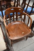 A late 19th or early 20th Century oak spindle back captains style office chair having turned frame