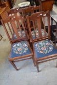 A set of four early 20t Century mahogany dining chairs having rail backs and woolwork drop in seats
