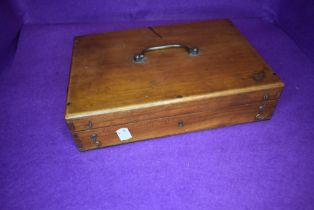 A mid century wooden box containing a number of pencils and stationary