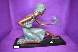 A reproduction art deco figure of a lady holding a parrot