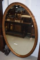 A late 19th or early 20th Century large giltwood/gesso wall mirror of oval form, having lozenge bead