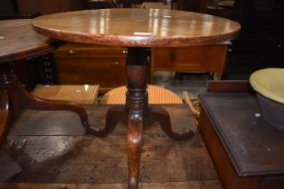 A 19th Century oak pedestal table, cut down height, having circular top over turned column and