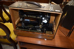 A traditional singer sewing machine, electric belt drive , numbered EG867846, in typical crocodile