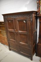 A period oak cabinet of panel form having double doors, carved frieze with monogram TB and '1678'