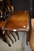 A traditional nest of three reproduction tables having cabriole legs and glass tops