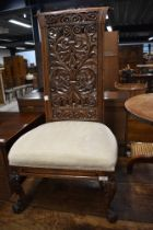 A traditional hardwood nursing chair, possibly Continental having inticrate back, scroll frame and