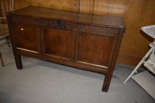 A period oak kist/coffer having typical carved frieze, two plank tip and triple panel front, some