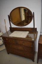 An early 20th Century oak dressing table having oval mirror back and two over two drawer base,