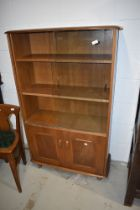 A vintage mid stain bookcase by Ercol, having glazed upper section with two adjustable shelves and