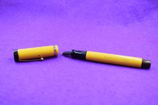 A Parker Duofold Lucky Curve button fill fountain pen in Mandarin yellow with single band to cap,