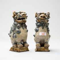 A pair of Chinese Tibetan styled figures of two dogs of Fo / Foo imperial temple guardian lions or