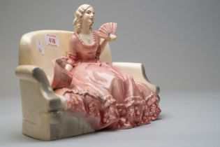 A katzhutte figurine of lady on sofa holding a fan with bonnet by her side in a pink period costume,