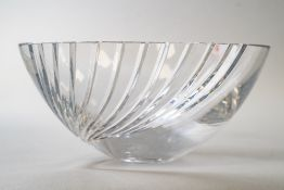 A modernist style clear cut crystal glass fruit bowl having a wave form expanding cut to one side