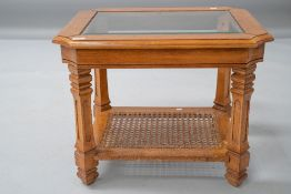 A modern stained frame coffee table having glazed top and bergere canework undertier, approx 68 x