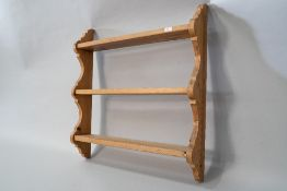 A natural pine triple wall shelf of small proportions with plate grooves to each and shaped ends,