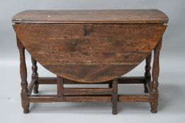 A period oak gateleg table having drawers to each end, on turned legs. Splitting to top and a few