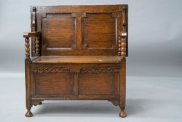 An early to mid 20th Century oak monks bench having plain top, panelled back and box section, bobbin