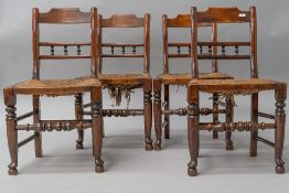 A set of four 19th Century spindle back kitchen chairs having rush seats, having rail and bobbin
